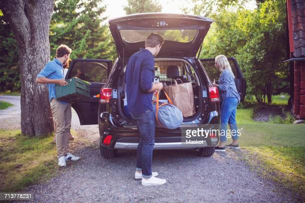 Friends loading luggage into car while standing on road