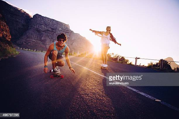 friends longboard skating on road sunset - skating stock photos and pictures