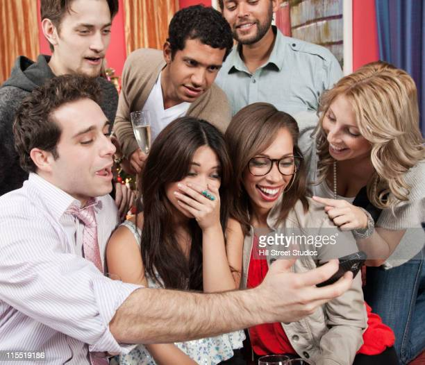 Friends looking at cell phone at party