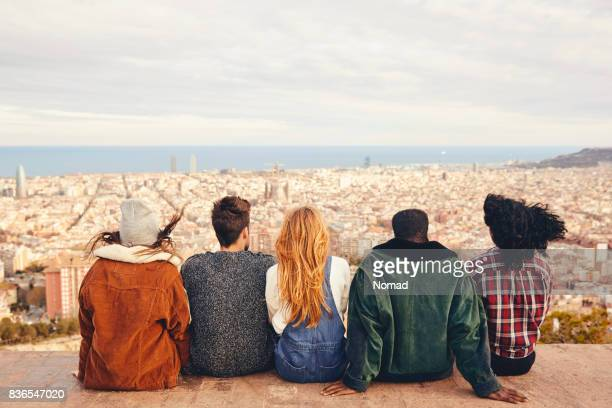 Friends looking at city while sitting on terrace