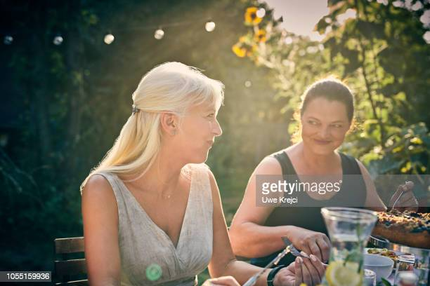 Friends looking at each other at garden party