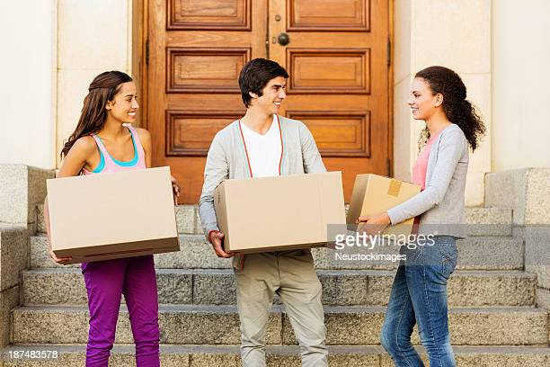Friends Looking At Girl While Carrying Cardboard Boxes On Steps