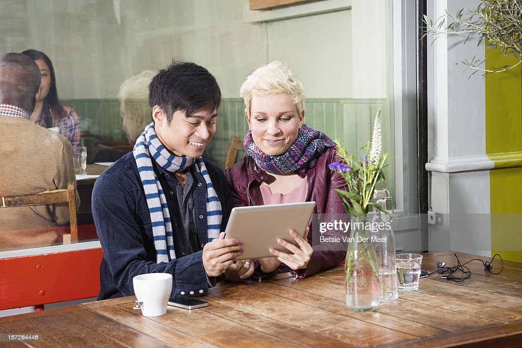 friends looking at ipad sitting at outdoor cafe : Foto de stock