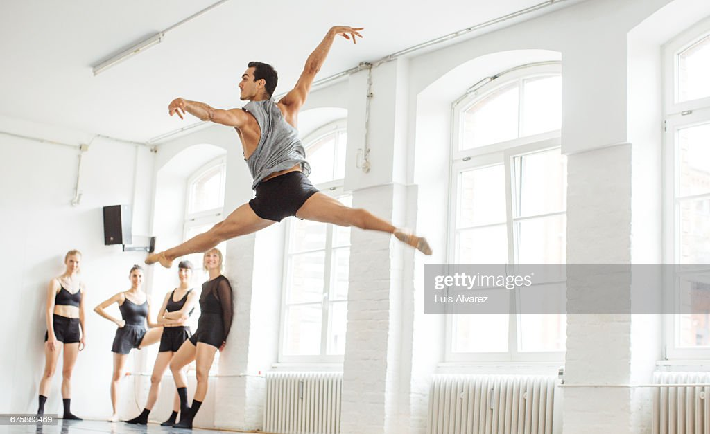 Friends looking at male ballet dancer in mid-air : Stock Photo