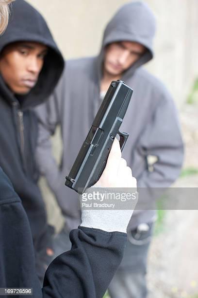 Friends looking at man holding gun