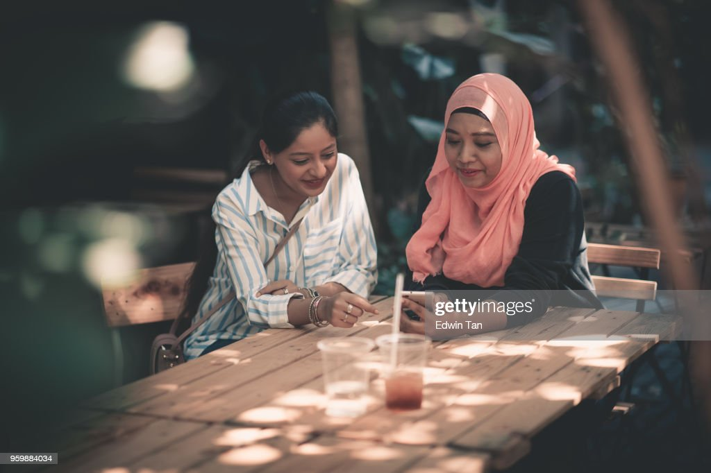 2 friends looking at mobile phone and talking to each other : Stock Photo
