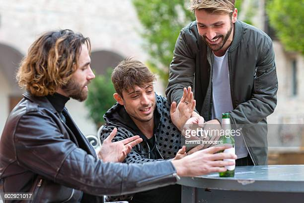 Friends looking at mobile phone while out drinking