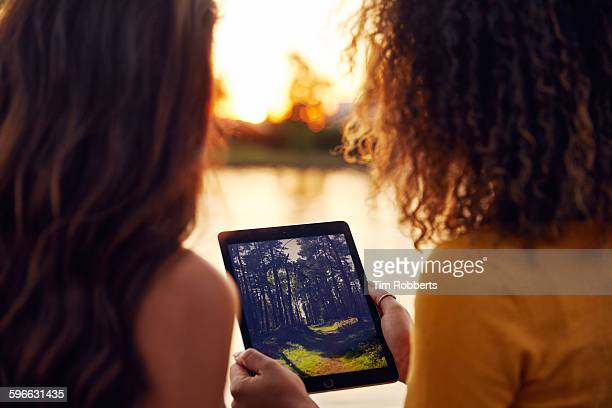 Friends looking at photo on tablet next to river.