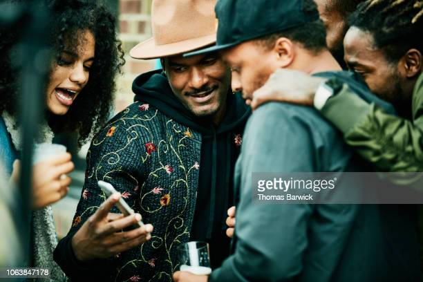 friends looking at smart phone during party at outdoor restaurant - influencer stock pictures, royalty-free photos & images