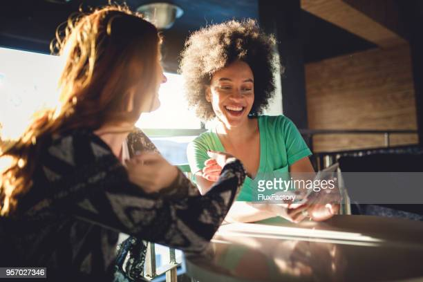friends looking at the mobile phone at the cafe - social media stock pictures, royalty-free photos & images