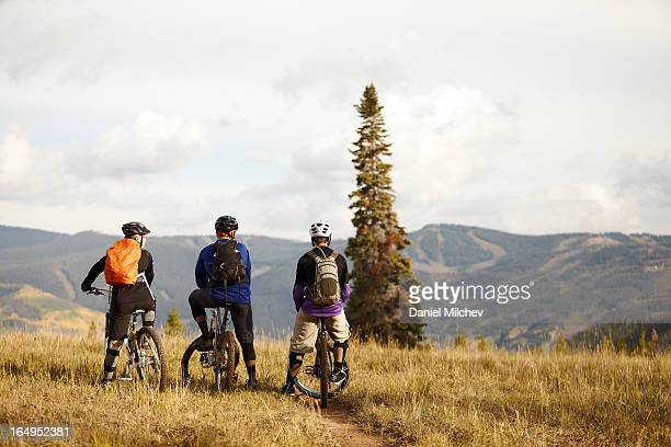 Friends looking at the mountains, sitting on bikes
