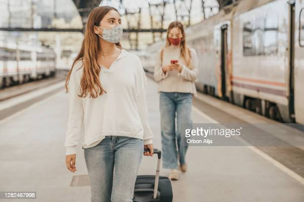 friends looking at the phone at train station - female friendship stock pictures, royalty-free photos & images