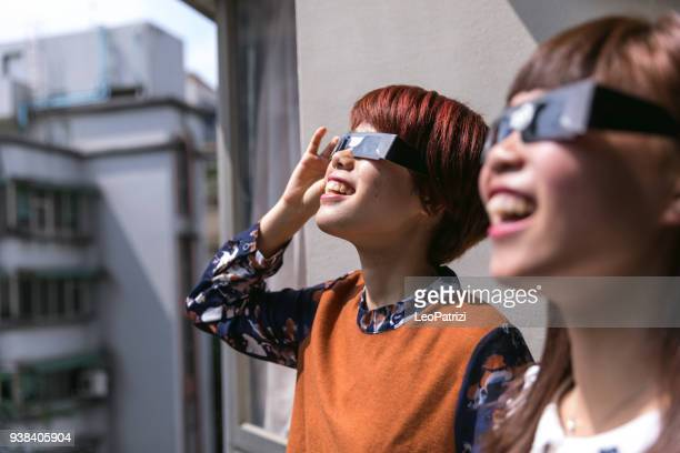 Friends looking at the solar eclipse for the first time