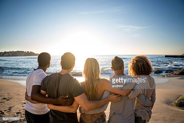 Friends looking at the sunset at the beach