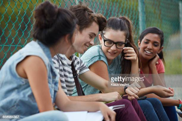 Friends looking at watch together at school