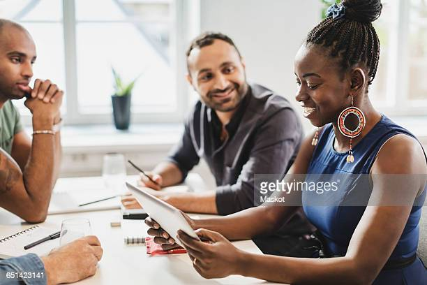 Friends looking at woman using digital tablet in language class