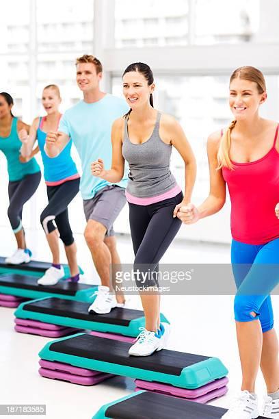 Amigos olhando para longe enquanto fazendo Aeróbica no ginásio com passos