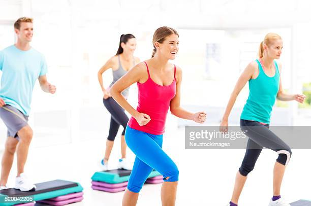 Amigos olhando para longe enquanto fazendo Aeróbica Step no ginásio