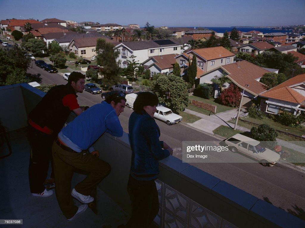 Friends looking down from a balcony : Stock Photo