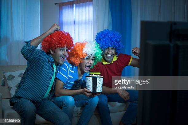 Friends looking excited while watching cricket match on the television at home
