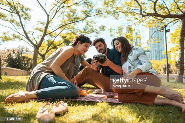 friends looking photos on digital camera - sentar se imagens e fotografias de stock