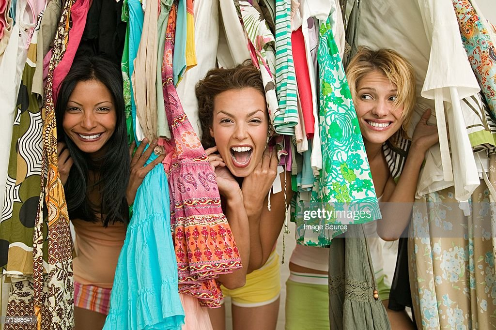 Friends looking through hanging clothes : Stock Photo