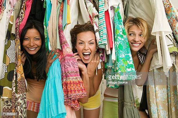 Friends looking through hanging clothes