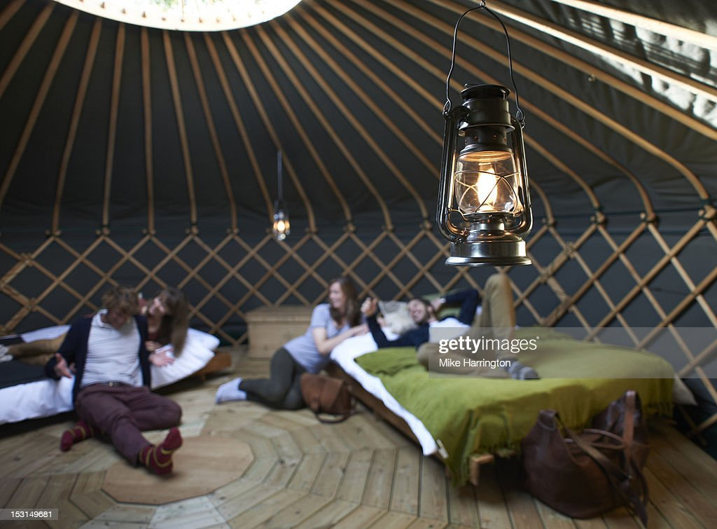 Friends lounging around beds inside yurt. : Stock Photo