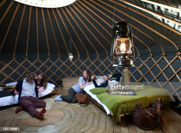 Friends lounging around beds inside yurt.