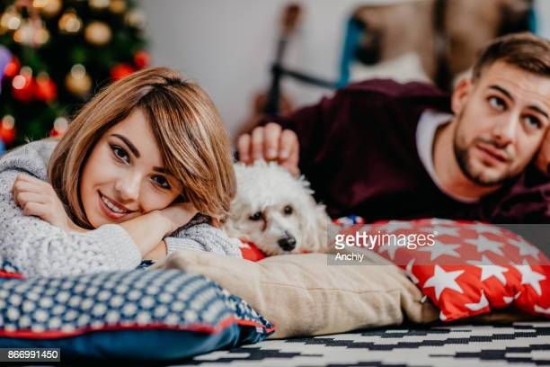 friends lying on the pillows with the dog in between, focus on a girl