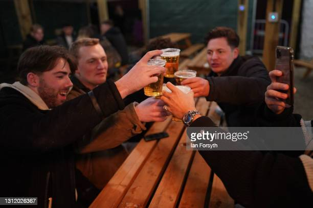 Friends make a toast as they enjoy a drink at the Switch bar in Newcastle shortly after midnight following the easing of lockdown measures on April...
