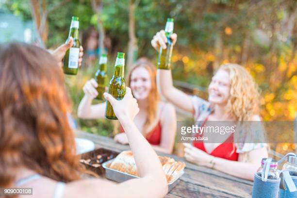 Friends making a celebratory toast with beer and having a picnic