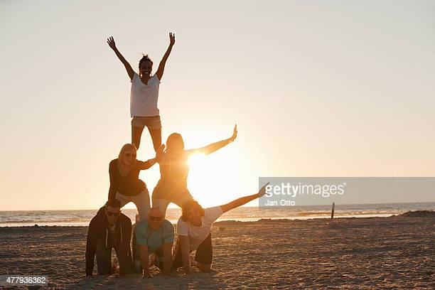 friends making a pyramid on the beach of st.peter-ording - pyramid stock pictures, royalty-free photos & images