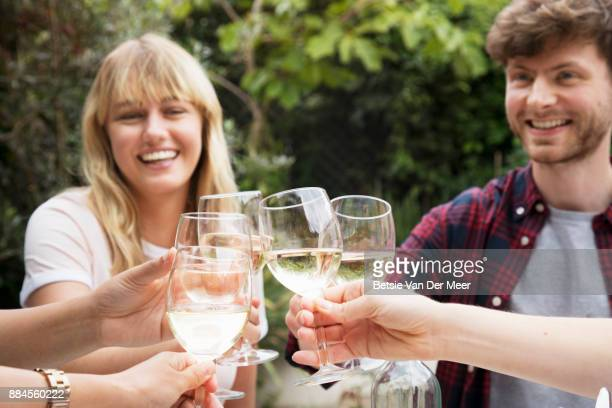 Friends making celebratory toast with wine glasses in garden.