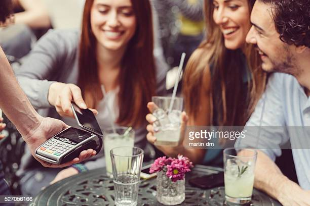 Friends making contactless payment with smartphone