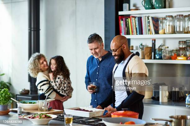 friends making dinner together, woman holding young girl - kitchen stock pictures, royalty-free photos & images