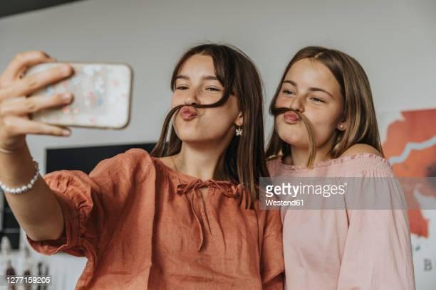 friends making fake mustache with hair while taking selfie at home - weiblicher teenager stock-fotos und bilder