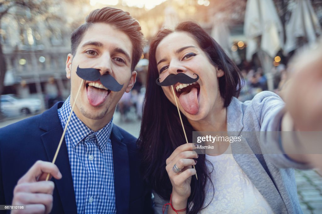 Friends making fake mustaches selfie on sunset : Stock Photo
