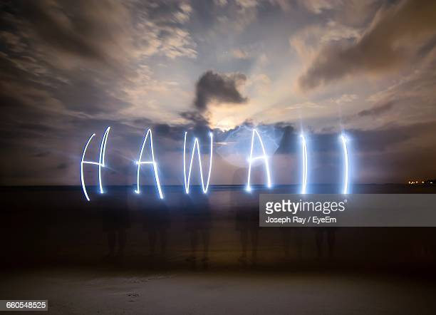 Friends Making Hawaii Text Through Lights At Beach During Sunset