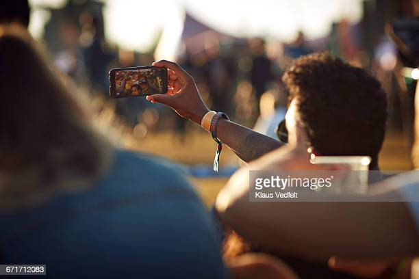 Friends making selfie at big festival concert