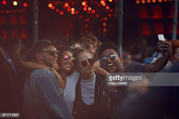 Friends making selfie at concert