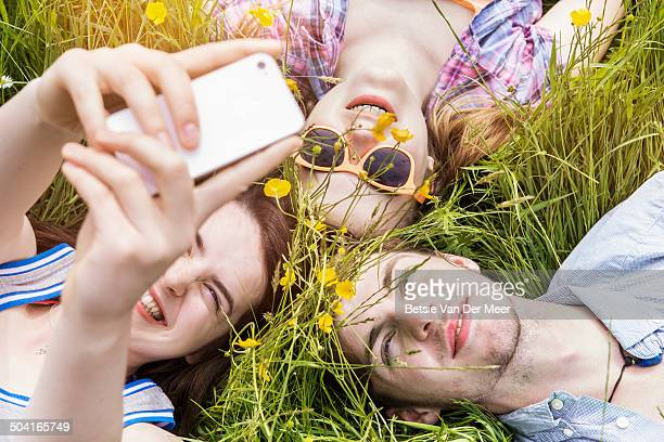 Friends making Selfie laying in grass.