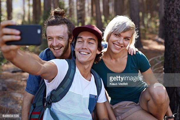 Friends making selfie on hiking trip in forrest