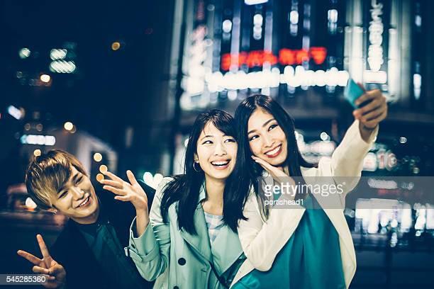 Friends making selfie on street at night