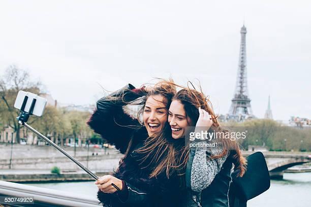 Friends making selfie with monopod in front of Eiffel tower