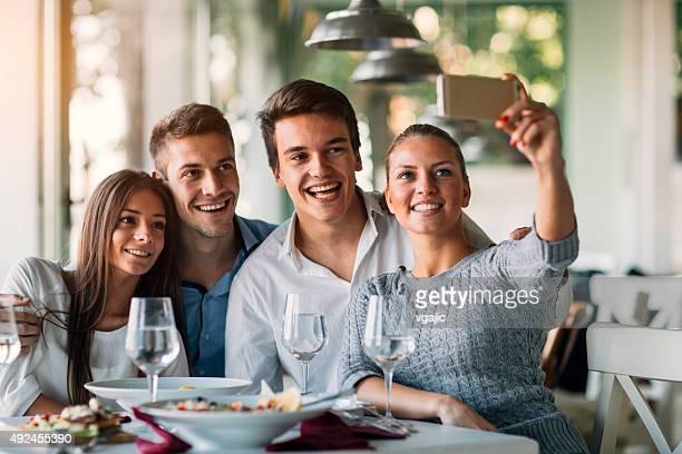 amigos fazendo selfie com telefone inteligente no restaurante. - quatro pessoas - fotografias e filmes do acervo