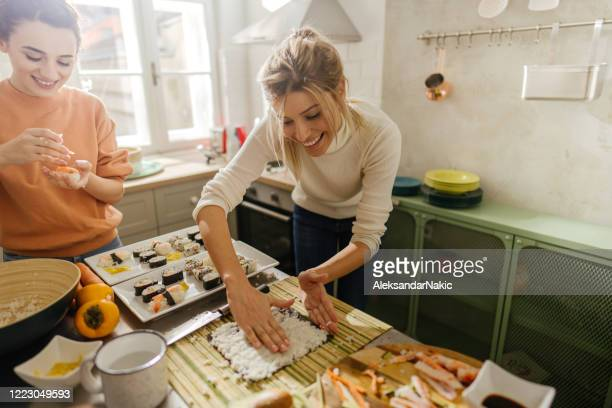 friends making sushi - sushi stock pictures, royalty-free photos & images