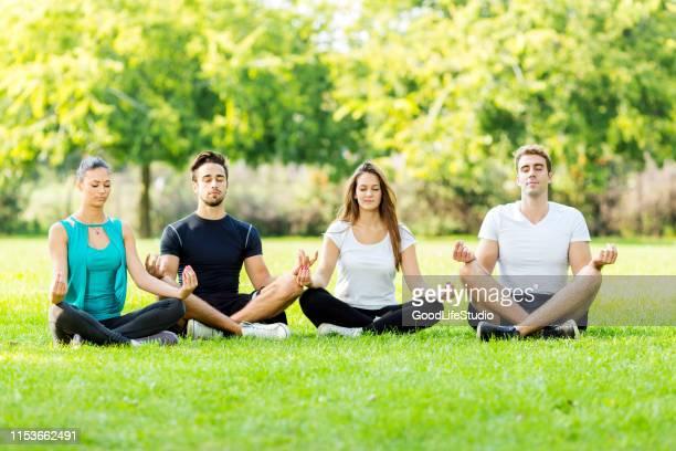 vrienden mediteren in park - lotuspositie stockfoto's en -beelden