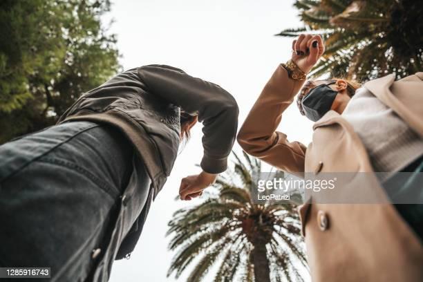 les amis se rencontrent dans la rue et évitent les poignées de main - éviter de se serrer la main photos et images de collection