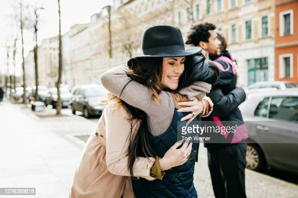 friends meeting and hugging in street - 30 39 years stock pictures, royalty-free photos & images